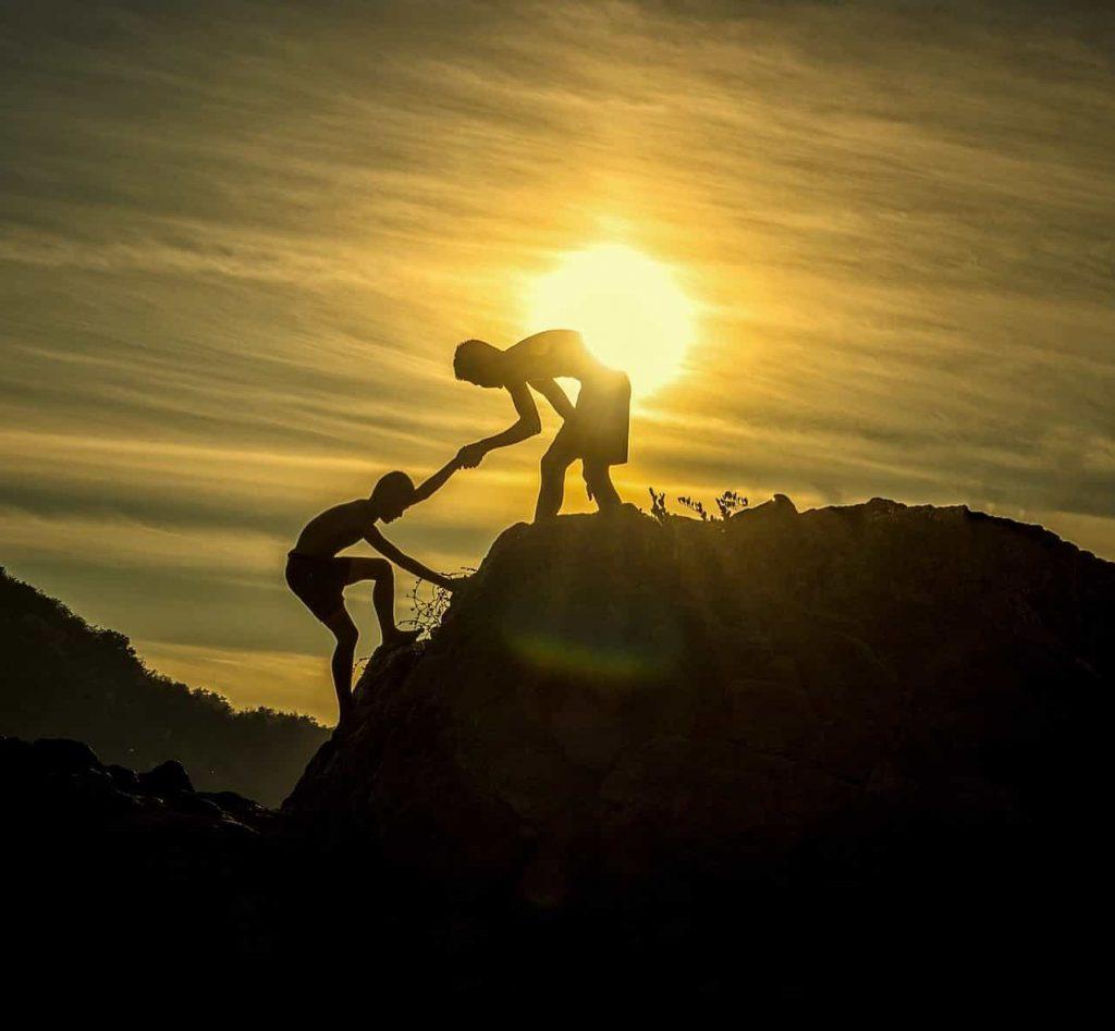 El Coach es un aliado clave para el Gerente del Proyecto, persona ayudando a otra a escalar una montaña