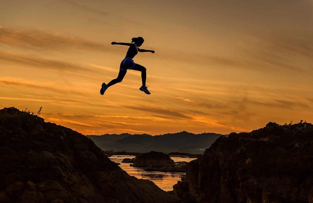 Coachee logrando metas, mujer saltando exitosamente